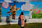 Glastonbury Festival 2014.<br /> Being photographed with a giraffe on the evolving graphic walls by Link Leisure give a dream like quality as you enter shangri La<br /> Shangri-La is the after-hours epicentre of Glastonbury Festival, a largely indescribable, ephemeral and interactive world that really comes to life after dark.<br /> Unique among festivals, Shangri-la has a central narrative that pins it all together,  it evolves year by year (a bit like Star Wars). All contributors respond to this narrative, and add to it via their installations, venues and performances. When it all comes together on site the audience have a wholly immersive world to become lost in with a myriad of places to explore.<br /> Exploration and discovery is an important aspect of  Shangri-la. A maze of covered alleys is riddled with nano-venues, performers and installations, artworks and hidden doors.<br />  In 2014 Shangri-La explored the way we create heavens and hells for ourselves.