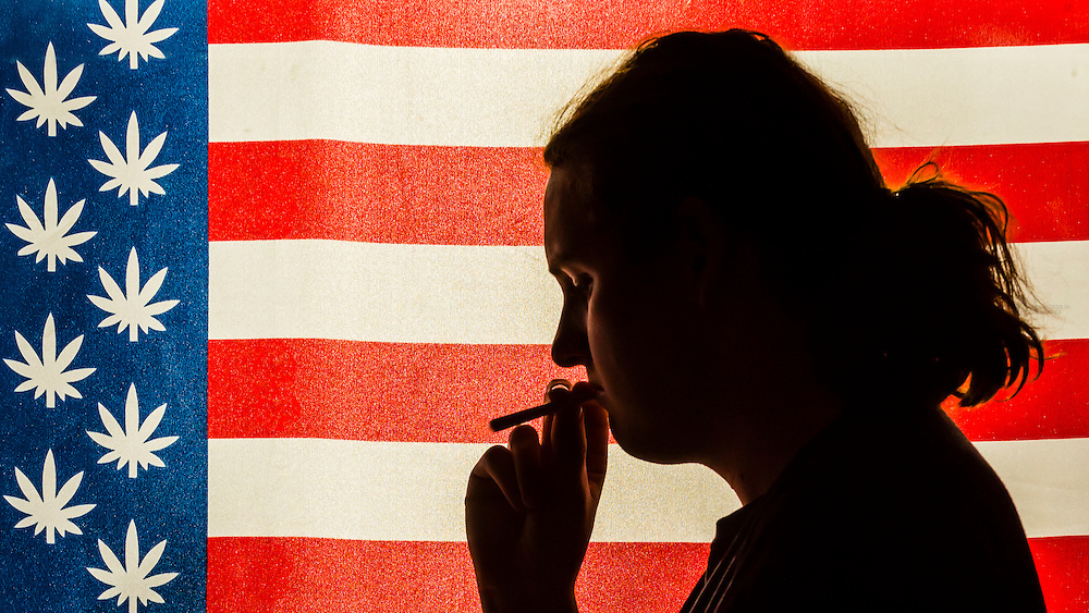 Man smoking a joint with American marijuana flag i background, Littleton, Colorado USA.  Colorado was the first state to legalize the sale of marijuana for recreational use in 2014.