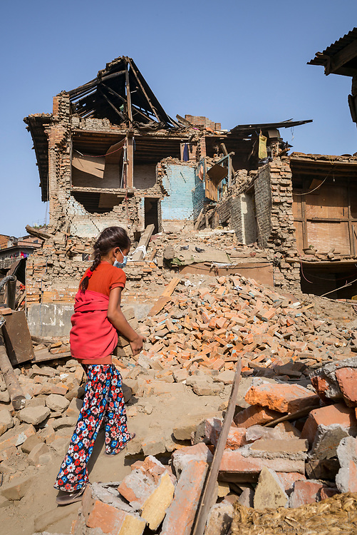 Eight year old Yamuna helps to clear rubble from the remains of her family home, destroyed by the 2015 Nepal earthquake.
