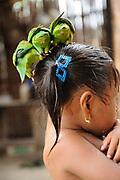 Indígenas guna / niña indígena con loros sobre la cabeza en la comarca de Guna Yala, Panamá.