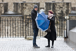 © Licensed to London News Pictures. 08/02/2019. London, UK.  A couple struggle to control their umbrella near the Tower of London during wet and windy weather. Storm Erik is the first named storm of 2019 with gale force winds and wet weather affecting most of the UK today. Photo credit: Vickie Flores/LNP