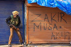 December 18, 2018 - Srinagar, Jammu & Kashmir, India - Indian policeman seen hiding himself in front of a closed store during clashes in Srinagar. Clashes erupted soon after the protestors were detained by Indian policemen in Srinagar during a march against the recent civilian killings. The march was called by Separatist leaders after the Indian army killed seven civilians in the Pulwama district of Jammu and Kashmir recently. (Credit Image: © Idrees Abbas/SOPA Images via ZUMA Wire)
