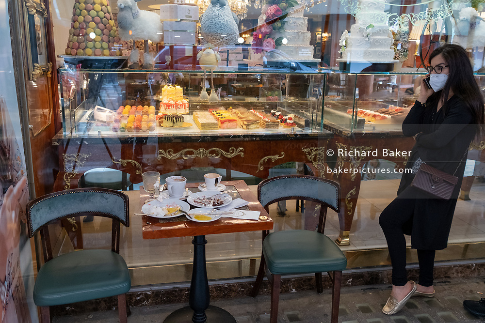 As a lady makes a call wearing a face covering, leftovers of empty cups and plates are seen outside a cafe selling cakes and pastries in Knightsbridge during the Coronavirus pandemic, on 24th August 2020, in London, England.