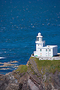 Speedboat passes Hartland Point Lighthouse, 19th Century Grade II listed, Atlantic Ocean and Bristol Channel in North West Devon, UK