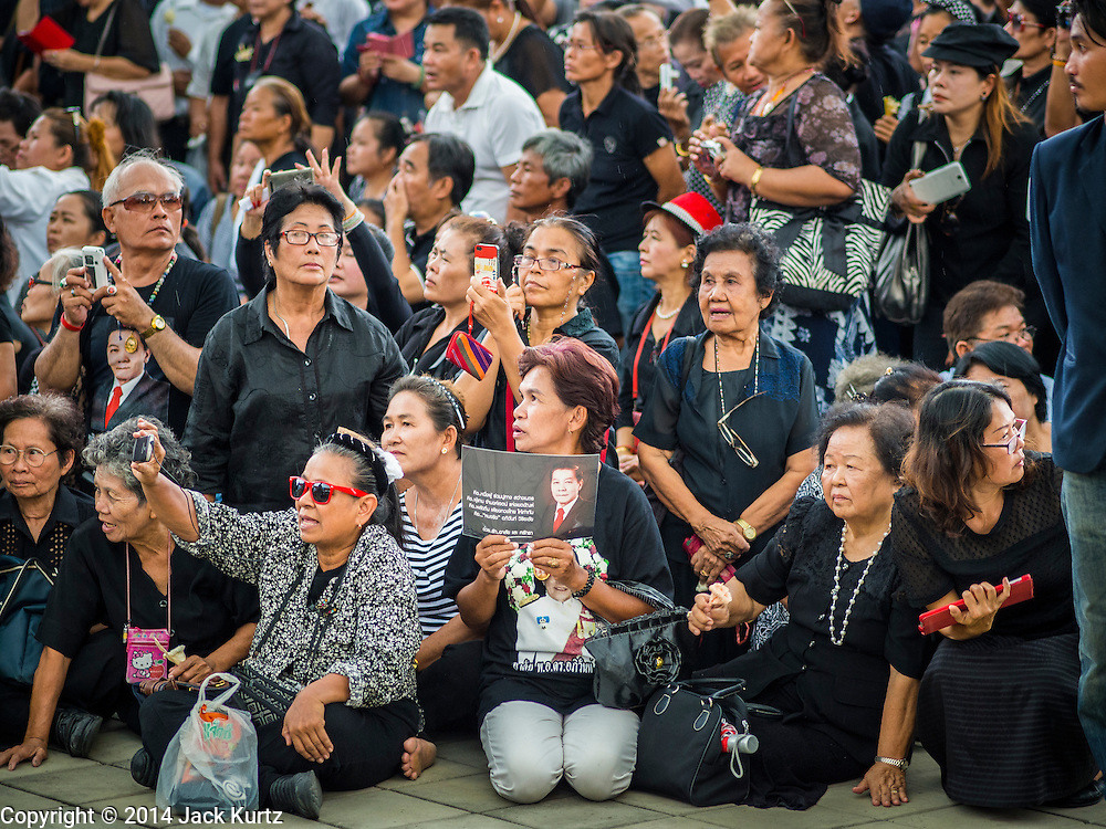 19 OCTOBER 2014 - BANG BUA THONG, NONTHABURI, THAILAND:  Mourners gather in the plaza at Wat Bang Phai for Apiwan Wiriyachai's cremation in Bang Bua Thong, a Bangkok suburb, Sunday. Apiwan was a prominent Red Shirt leader. He was member of the Pheu Thai Party of former Prime Minister Yingluck Shinawatra, and a member of the Thai parliament and served as Yingluck's Deputy Prime Minister. The military government that deposed the elected government in May, 2014, charged Apiwan with Lese Majeste for allegedly insulting the Thai Monarchy. Rather than face the charges, Apiwan fled Thailand to the Philippines. He died of a lung infection in the Philippines on Oct. 6. The military government gave his family permission to bring him back to Thailand for the funeral. His cremation was the largest Red Shirt gathering since the coup.    PHOTO BY JACK KURTZ