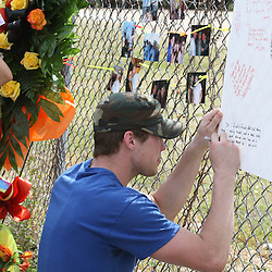(Shot on March 6, 2009) Chris Hill writes on a memory wall put up on a fence along side the scene of a fatal hit and run accident that involved Hill's roommate Thurman 'Rion' Lowe who was one of three students killed while walking home shortly after 2:00am on the morning of March 6, 2008 on Nashville Street in Hammond, Louisiana after a drunk driver hit five students killing three and critically injuring one and leaving one student with minor injuries, the driver identified as 21-year-old Derek Quebedeaux also a Southeastern student was arrested by Hammond Police, Quebedeaux was also a roommate of Lowe and Hill.. (Photo by: Derick Hingle)
