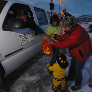 Daryll Hedman, Manitoba Conservation officer, hands out candy on Halloween night to kids on the streets of Churchill, Manitoba.