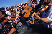 Musicians from the famous Doerr family, play guitars and violins in the surf after the procession of Saint Sara. Music is their life blood, an essential part of Roma, Gitan and Manouche culture. Often a singer will improvise on an old song, singing praises on homage to someone or of love or sorrow, of persecution ill treatment. Their history is often remembered, and shared in songs rather than written down<br /><br />Europe, France, Camargue, Saintes Maries de la Mer. Gypsy music, dance and occasionally even bears are part of the traditional culture brought by Gypsies to the festival at Saintes Maries de la Mer, May every year. The Gypsy pilgrimmage brings gypsies from all over Europe for their annual festival.