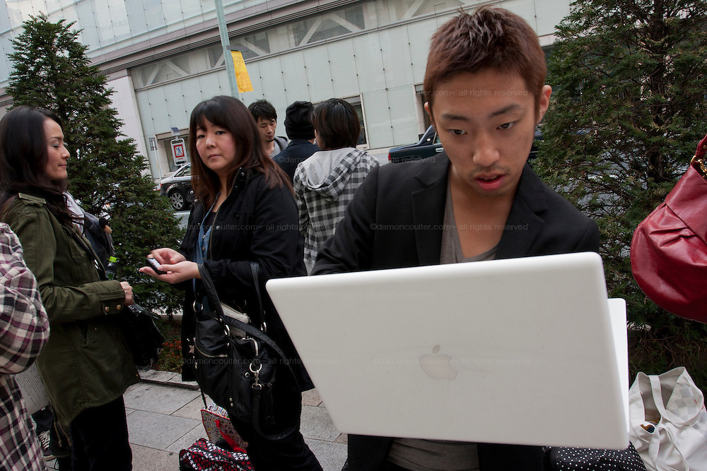 Takachiyo Yamanaka broadcasts from his Apple mac laptop computer as he stands in the lines of people at the Apple store awaiting the official release of the iphone4S in Ginza, Tokyo, Japan. Friday October 14th 2011. The latest version of the popular iphone was released worldwide on October 14th. Japans flagship Apple store in Ginza was opened at 8am for the 800 people that had been waiting to be the first to purchase the new telephone.