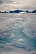 Melt water pools and jagged peaks on the Greenland Ice cap during a British mountaineering expedition to Knud Rasmussens Land, East Greenland, Arctic, 2006.