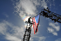 Firefighters mount an American flag on ladder trucks at Monday's ceremony in Salinas celebrating the completion of the Prunedale Improvement Project for Route 101.