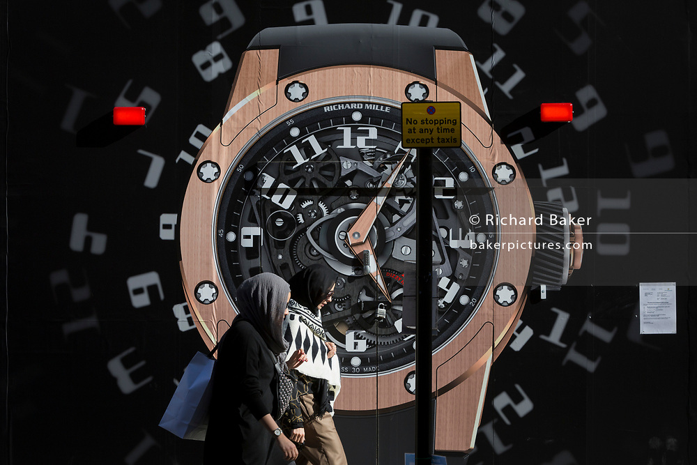 Two Mulsim women walk past a construction hoarding of a watch outside the new Richard Mille shop in New Bond Street, on 25th February 2019, in London, England.