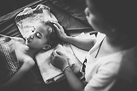 Namfon, aged 6, suffers from Japanese Encephalitis at a hospital in Vientiane, Laos. Her mother, Teo, leans over to comfort her.