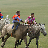 Young, costumed bareback riders approach the end of a 20km race at a traditional naadam festival on a remote pass near Muren, Mongolia.