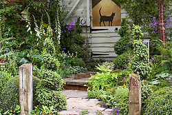 Stone path leading to weatherboarded building with stable door. Cat trompe-l'oeil painting. Spiral box topiary. A Shady Courtyard Garden. Design: Fiona Bruce - Chelsea 2005