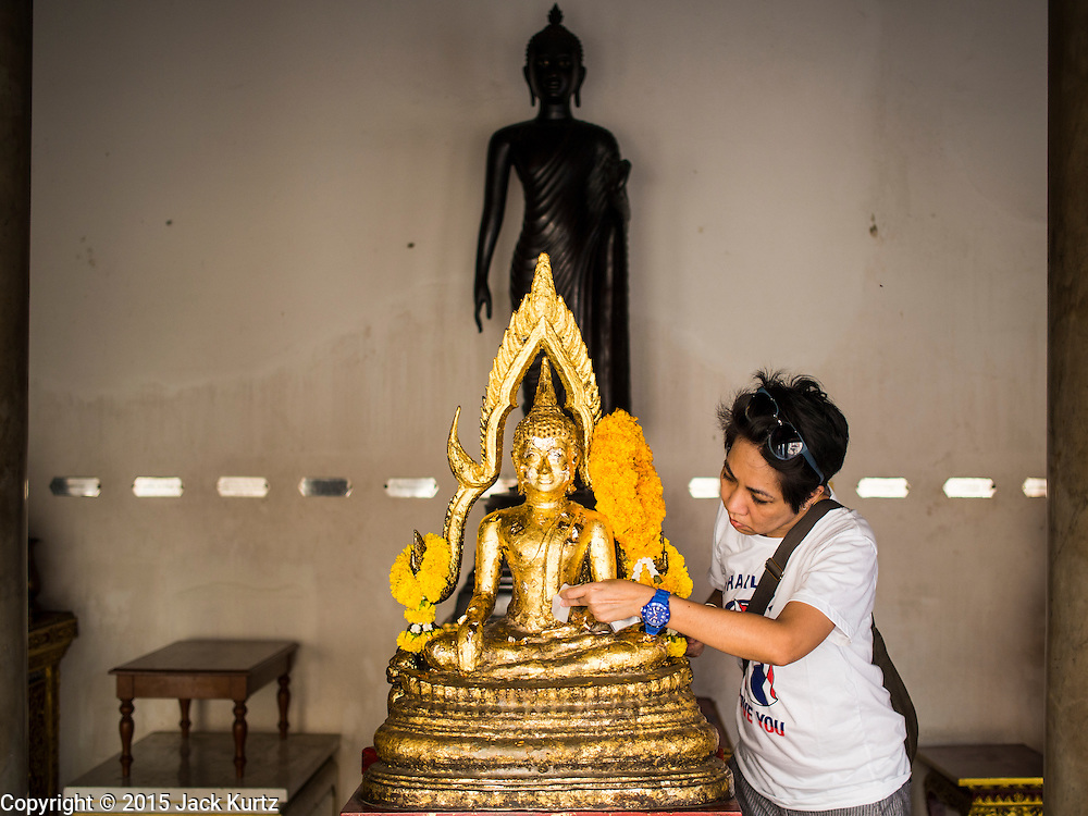 04 MARCH 2015 - BANGKOK, THAILAND: A woman applies gold leaf to a statue of the Buddha at Wat Benchamabophit on Makha Bucha Day. Makha Bucha Day is an important Buddhist holy day and public holiday in Thailand, Cambodia, Laos, and Myanmar. Many people go to temples to perform merit-making activities on Makha Bucha Day. Wat Benchamabophit is one of the most popular Buddhist temples in Bangkok.    PHOTO BY JACK KURTZ