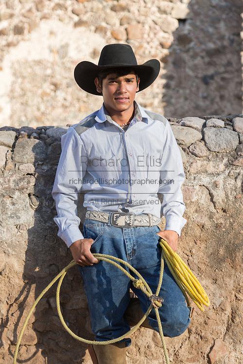 A Mexican charro or cowboy poses in cowboy hat and lasso at a hacienda ranch in Alcocer, Mexico.
