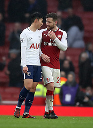 Arsenal's Shkodran Mustafi (right) chats with Tottenham Hotspur's Son Heung-Min (left) after the end of the match