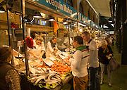 People shopping at fishmonger stalls inside historic covered market building, Jerez de la Frontera, Spain