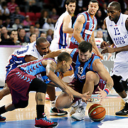 Anadolu Efes's Dontaye Draper (L), Stephane Lasme (R) and Trabzonspor's Andrija Stipanovic (C), Jerome Randle (F) during their Turkish Basketball League match Anadolu Efes between Trabzonspor at Abdi Ipekci Arena in Istanbul Turkey on Sunday 19 October 2014. Photo by Aykut AKICI/TURKPIX