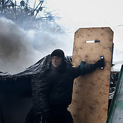January 25, 2014 - Kiev, Ukraine: A anti-government protestor uses a homemade shield to protect himself from the riot police water canons at a barricade outside the Dynamo Kiev stadium, near the Independence Square in central Kiev. (Paulo Nunes dos Santos)