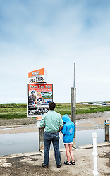 Tourists looking at a poster for seal boat trips, Blakeney, Norfolk
