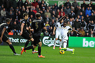 Swansea city's Roland Lamah ® has a shot at goal blocked. Barclays Premier league, Swansea city v Manchester City at the Liberty Stadium in Swansea,  South Wales on  New years day Wed 1st Jan 2014 <br /> pic by Andrew Orchard, Andrew Orchard sports photography.