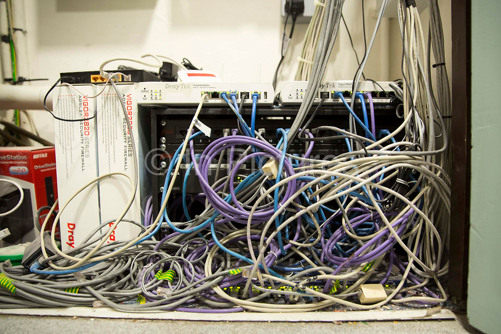 A mass of multicoloured computer cables out the back of a computer server in London, England, United Kingdom.