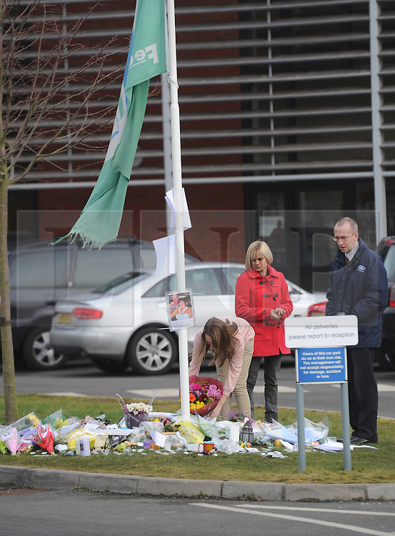 © Licensed to London News Pictures. 20/02/2012. Alvechurch, UK. A young girl, who has been brought in by her parents, lays flowers at a memorial in the school grounds of Alvechurch Middle School following the coach crash which claimed the life of one of their teachers, 52 year old Peter Rippington.  The accident, which happened following a skiing trip in France has also left 10 other children injured with one remaining critically ill.    Photo credit: Alison Baskerville/LNP