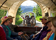 Tourists enjoy the short ride to Cache Creek in a train of covered wagons Saturday, on their way to the Bar T 5 Covered Wagon Cookout. The experience includes a wagon ride, a dramatic indian attack, chuck wagon dinner and live music.