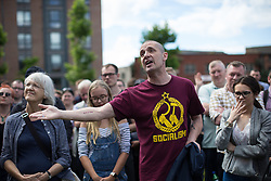 © Licensed to London News Pictures . 30/07/2016 . Liverpool , UK . A member of the crowd remonstrates with Owen Smtih at an Owen Smith rally in a field off Bridgewater Street in Liverpool . The booked venue , the Camp and Furnace warehouse , reportedly cancelled the booking . Smith is campaigning to replace Jeremy Corbyn as the leader of the Labour Party . Photo credit : Joel Goodman/LNP
