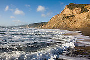 Waves roll up against high coastal bluffs along narrow Wildcat Beach in Point Reyes National Seashore, California.