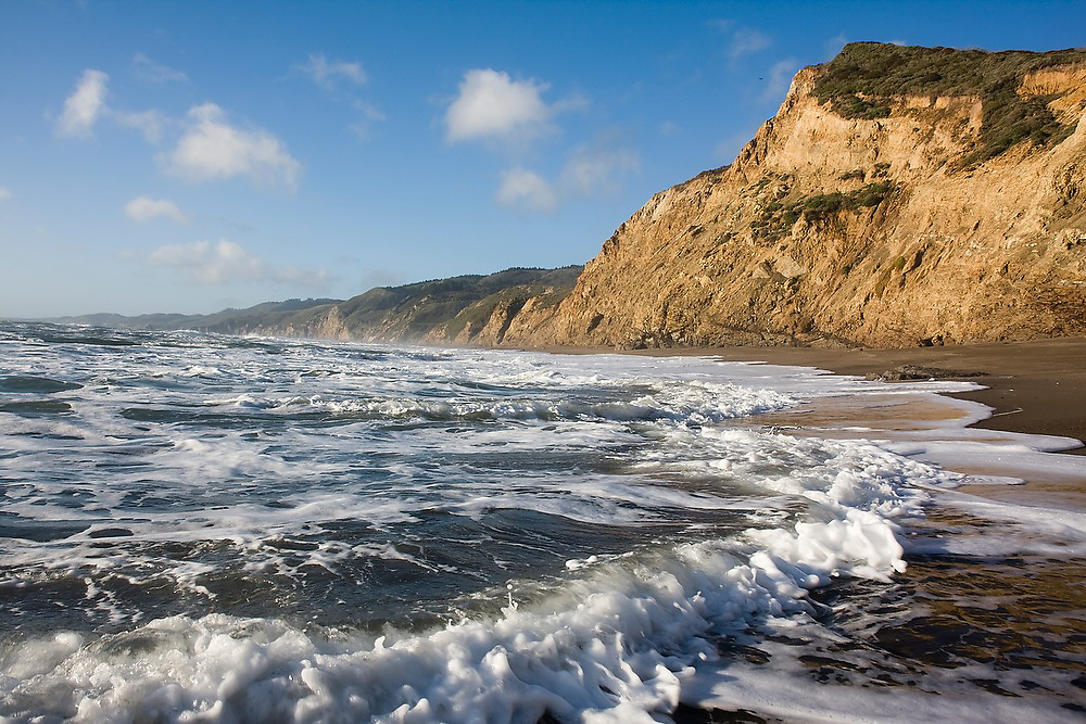 Waves roll up against high coastal bluffs along narrow Wildcat Beach in Point Reyes National Seashore, California.