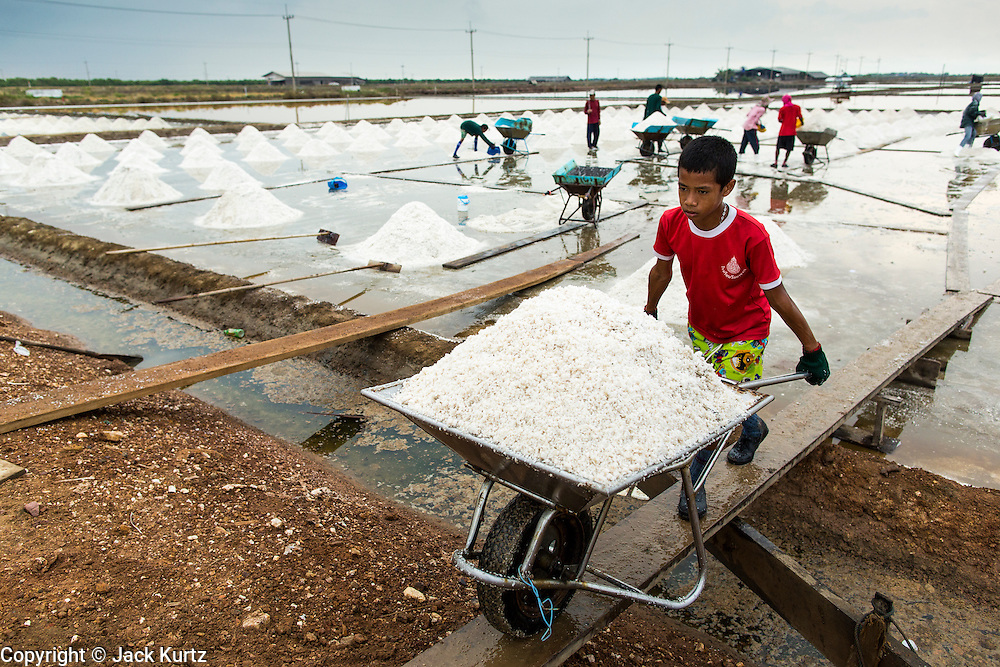 24 APRIL 2013 - SAMUT SONGKHRAM, SAMUT SONGKHRAM, THAILAND:    A child pushes a wheelbarrow of salt to an area where it will be bagged and weighed for sale. The 2013 salt harvest in Thailand and Cambodia has been impacted by unseasonably heavy rains. Normally, the salt fields are prepped for in December, January and February, when they're leveled and flooded with sea water. Salt is harvested from the fields from late February through May, as the water evaporates leaving salt behind. This year rains in December and January limited access to the fields and rain again in March and April has reduced the amount of salt available in the fields. Thai salt farmers are finishing the harvest as best they can, but the harvest in neighboring Cambodia ended 6 weeks early because of rain. Salt has traditionally been harvested in tidal basins along the coast southwest of Bangkok but industrial development in the area has reduced the amount of land available for commercial salt production and now salt is mainly harvested in a small part of Samut Songkhram province.   PHOTO BY JACK KURTZ