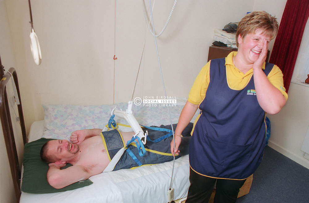 Carer and disability person sharing a joke while preparing to use hoist for bed transfer,
