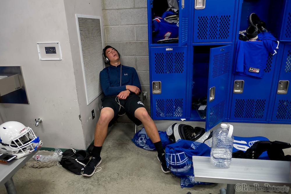 An Oak Ridge Trojan sleeps gets ready inside the locker room before the game as the Folsom High School Bulldogs varsity football team host the Oak Ridge High School Trojans,  Friday Nov 4, 2016.<br /> photo by Brian Baer