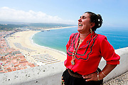 A nazarene dressed in the tradicional costume of Nazaré, The Seven Skirts, in the Sítio da Nazaré with a view of the town and the beach of Nazaré, Portugal. PHOTO PAULO CUNHA/4SEE