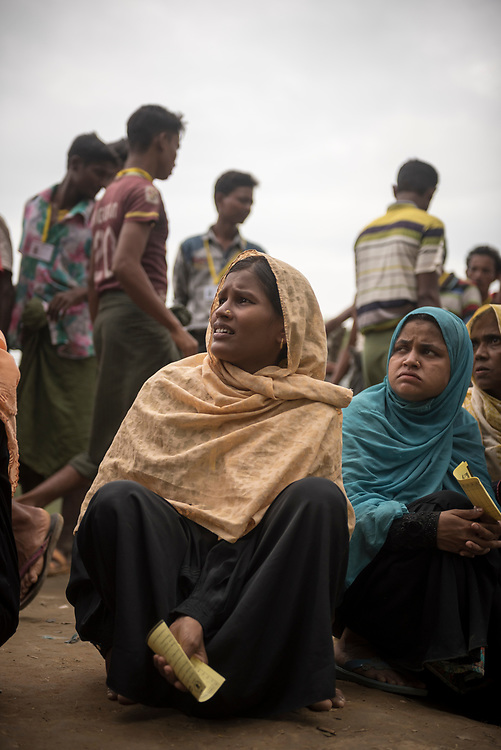 Rohingya women and men wait in line for a humanitarian aid distribution at Chakmarkul refugee camp in Bangladesh.