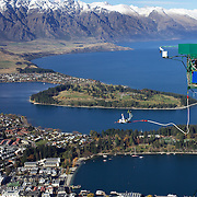 A participant jumps from the famous AJ Hackett Bungy Jump ' The Ledge' above Queenstown, New Zealand. The Bungy jump comes equipped with a runway to launch out 400 metres over Queenstown. with the snow capped Remarkables Mountain Range providing a stunning backdrop. Queenstown, Central Otago, South Island, New Zealand. 18th May 2011. Photo Tim Clayton..