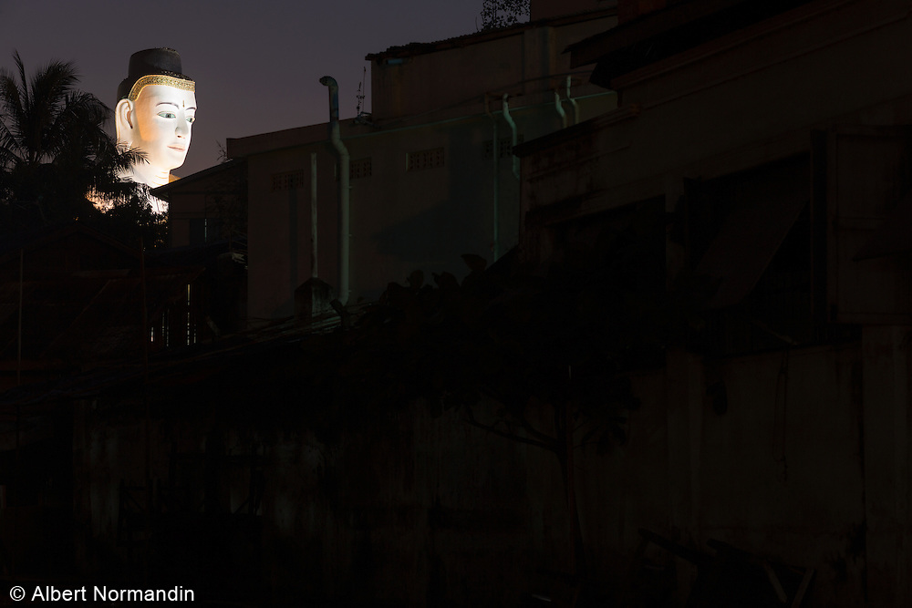 Buddha statue head with light over rooftops, Pyay