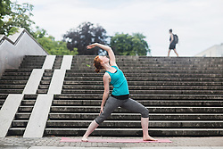 Young woman doing yoga on staircases in urban city, Freiburg im Breisgau, Baden-Wuerttemberg, Germany