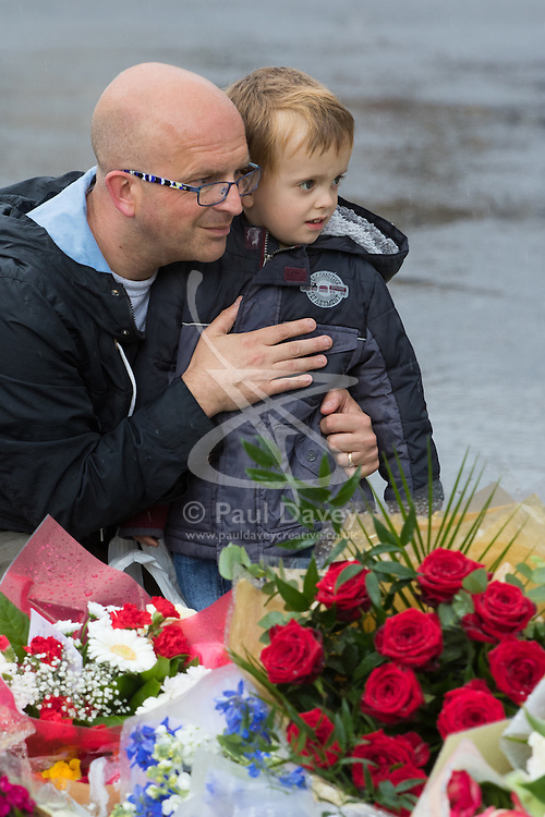 Parliament Square, Westminster, London, June 17th 2016. Following the murder of Jo Cox MP friends and members of the public lay flowers, light candles and leave notes of condolence and love in Parliament Square, opposite the House of Commons. PICTURED: A man and a boy look at the hundreds of bouquets and written tributes.