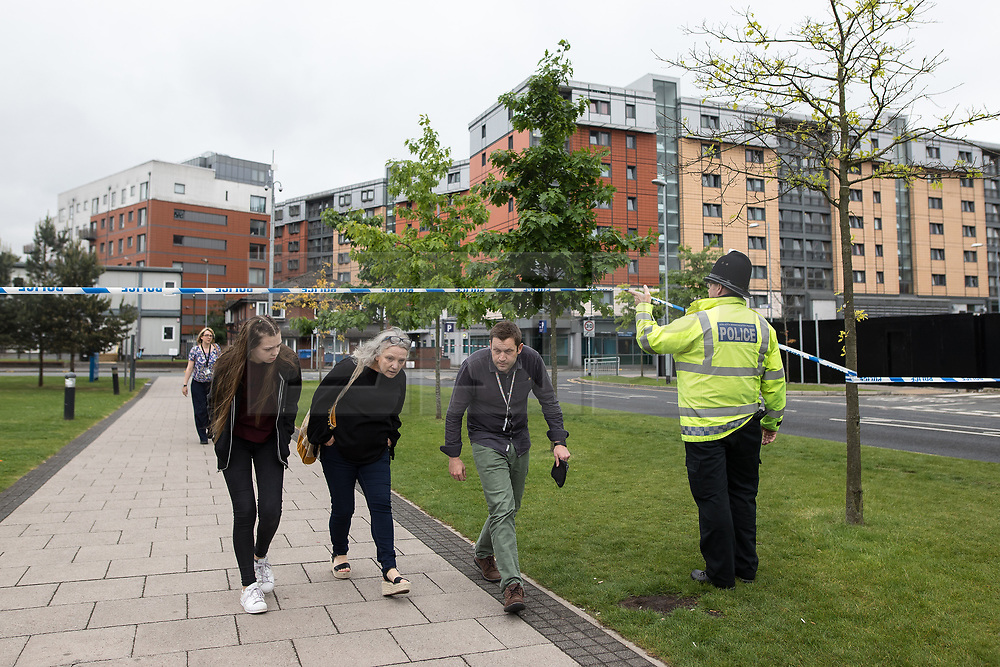 © Licensed to London News Pictures . 02/06/2017 . Manchester , UK . People are evacuated from surrounding buildings as police erect a 100m cordon around Banff Road after a car , which they say is significant in their investigation in to Salman Abedi , is discovered at Devell House , during a visit by the Duke of Cambridge , Prince William , at Royal Manchester Children's Hospital . The prince was meeting patients affected by the murderous bomb attack at an Ariana Grande gig at Manchester Arena on Monday 22nd May . Photo credit : Joel Goodman/LNP
