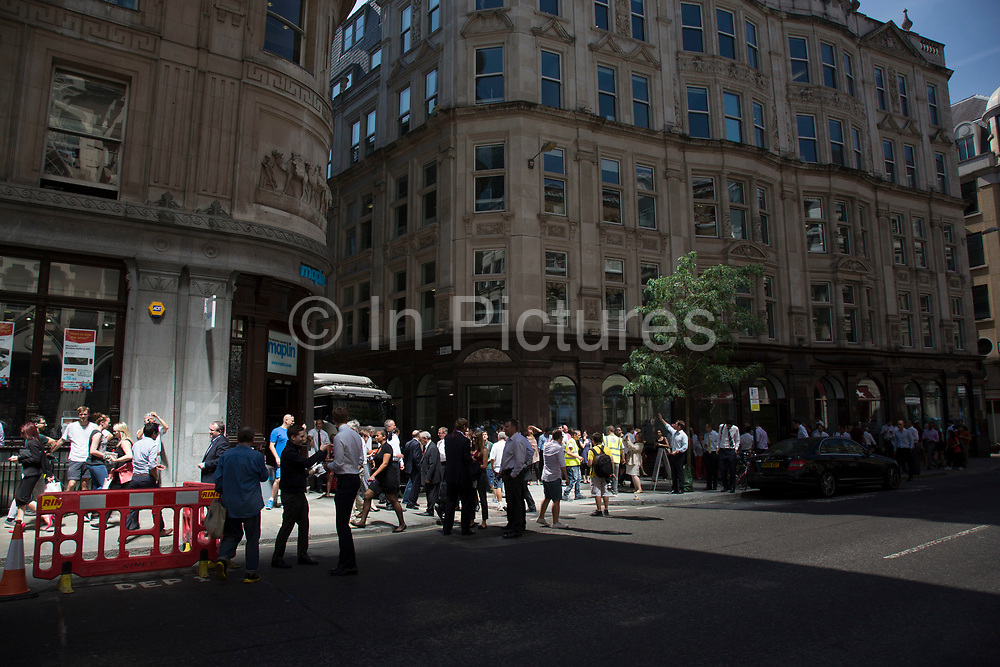 """London, UK. Thursday 5th September 2013. Wide view of the light landing on the pavement on Eastcheap. Urgent action in planned to """"cover up"""" the Walkie Talkie skyscraper in the City after sunlight reflected from the building melted a car on the streets below. Temperatures have been measured in excess of 50 degrees C, and as much as 70 degrees at it's peak. The 525ft building has been renamed the """"Walkie Scorchie"""" after its distinctive concave surfaces reflected a dazzling beam of light which has caused extensive damage to nearby buildings."""