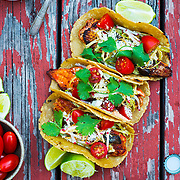 Fish tacos on rustic tabletop with guacamole beer and lime wedges