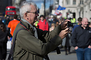 The Magnum photographer Martin Parr takes a photo for some tourists whie visiting Parliament Square, on 14th March 2019, in Westminster, London, England.