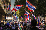 """14 JANUARY 2014 - BANGKOK, THAILAND:  Anti-government protestors wave Thai flags on Rama I Road in front of Royal Thai Police headquarters. Hundreds of protestors picketed police headquarters because they accuse the police of siding with the government during the protests. Tens of thousands of Thai anti-government protestors continued to block the streets of Bangkok Tuesday to shut down the Thai capitol. The protest, """"Shutdown Bangkok,"""" is expected to last at least a week. Shutdown Bangkok is organized by People's Democratic Reform Committee (PRDC). It's a continuation of protests that started in early November. There have been shootings almost every night at different protests sites around Bangkok, but so far Shutdown Bangkok has been peaceful. The malls in Bangkok are still open but many other businesses are closed and mass transit is swamped with both protestors and people who had to use mass transit because the roads were blocked.    PHOTO BY JACK KURTZ"""