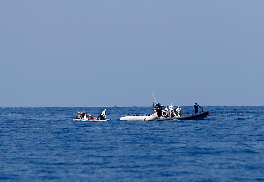 Italian Navy RHIBs (rigid hulled inflatable boats) from the ship Francesco Mimbelli surround a rubber dinghy carrying migrants during a rescue operation off the coast of Libya August 6, 2015.  More than 200 migrants are feared to have drowned in the latest Mediterranean boat tragedy after rescuers saved over 370 people from a capsized boat thought to be carrying 600, the Italian coast guard indicated on Thursday.<br /> REUTERS/Darrin Zammit Lupi <br /> MALTA OUT. NO COMMERCIAL OR EDITORIAL SALES IN MALTA