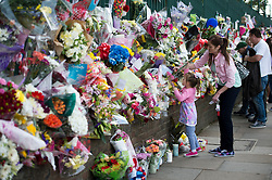 © London News Pictures. 25/05/2013. Woolwich, UK. A woman and her daughter laying flowers at the scene where Drummer Lee Rigby was murdered by two men in Woolwich town centre in what is being described as a terrorist attack. Photo credit: Ben Cawthra/LNP