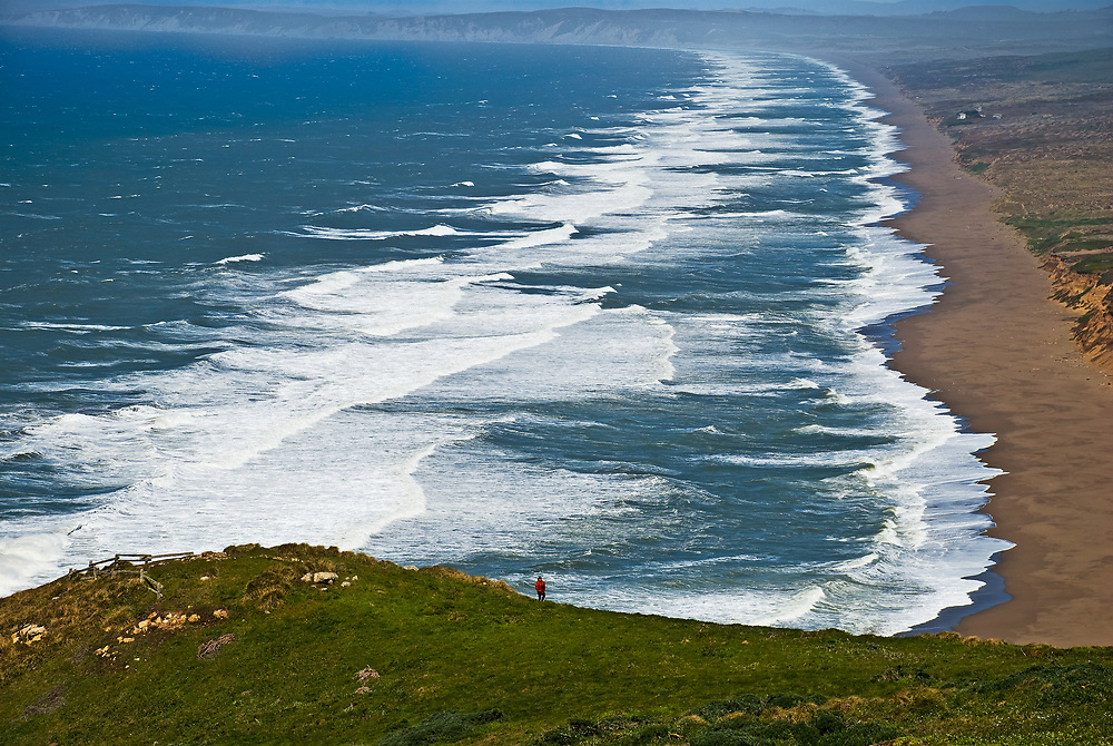 SUBJECT: Point Reyes Beach, California. IMAGE: Lone figure lends scale to the beach and surf streaching some 17 miles, kicking up spume causing distant mist.